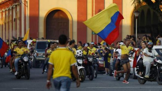 Varias personas celebran el pase a cuartos de la selección colombiana en una calle del municipio de Ginebra en el departamento del Valle del Cauca (Colombia).