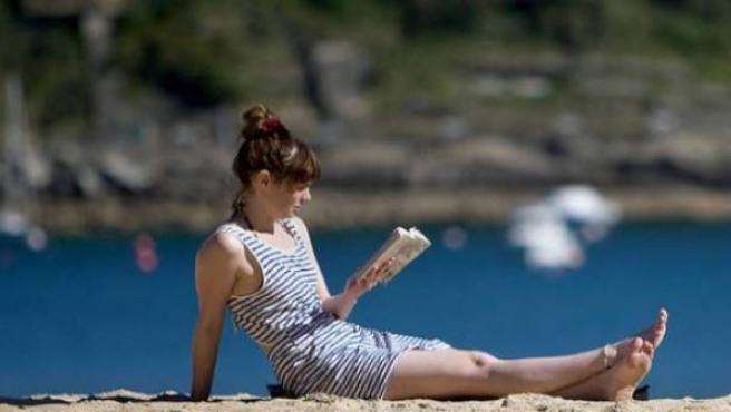 Una chica leyendo en la playa.