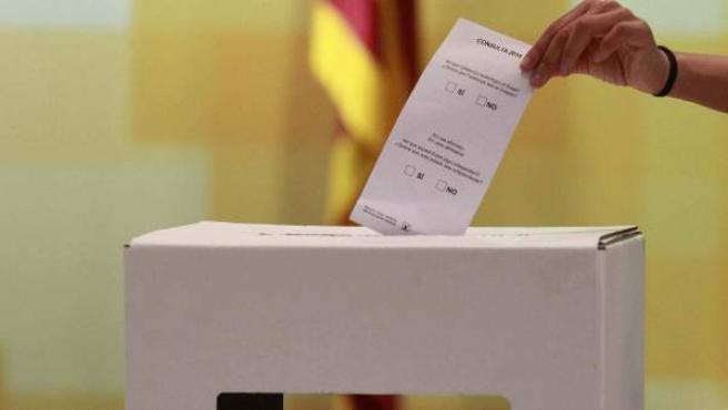 Una persona introduce una papeleta con las preguntas en el modelo de urna que La Generalitat fabricará para la celebración de la eventual consulta soberanista del próximo 9 de noviembre.