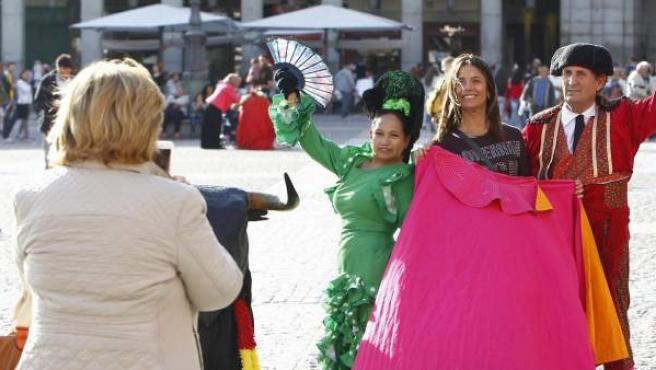 Unas turistas se hacen fotos con dos personas vestidas de torero y flamenca en la Plaza Mayor de Madrid.