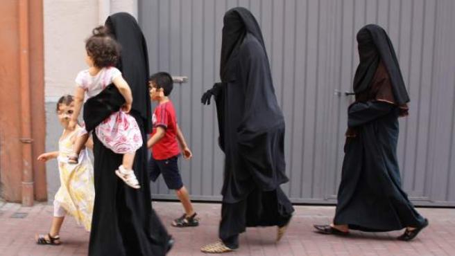 Tres mujeres con velo integral pasean por el centro de Lleida con tres niños.