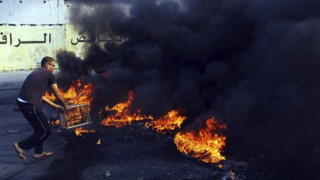 Un seguidor del presidente destituido, Mohammed Morsi, se acerca a una barricada ardiendo durante una protesta en las calles de El Cairo.