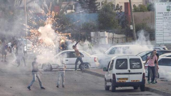 Manifestantes palestinos en la ciudad Arara (Israel) protestan contra la Policía israelí por el asesinato del joven palestino Mohamad Abu Jedir.