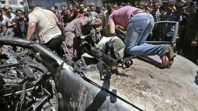 Varias personas observan los daños tras un ataque de las fuerzas israelíes en Gaza.