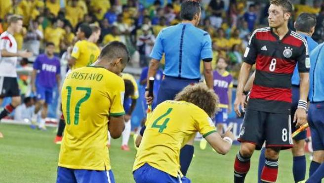 David Luiz y Luiz Gustavo de rodillas ante Özil tras la paliza de Alemania a Brasil.