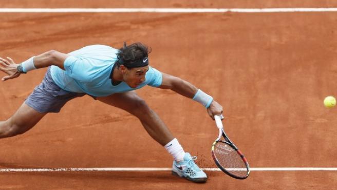 El tenista español Rafael Nadal, número uno en el ránking mundial, se estira para golpear la bola durante su partido de la segunda ronda del Roland Garros disputado contra el austríaco Dominic Thiem en París (Francia).