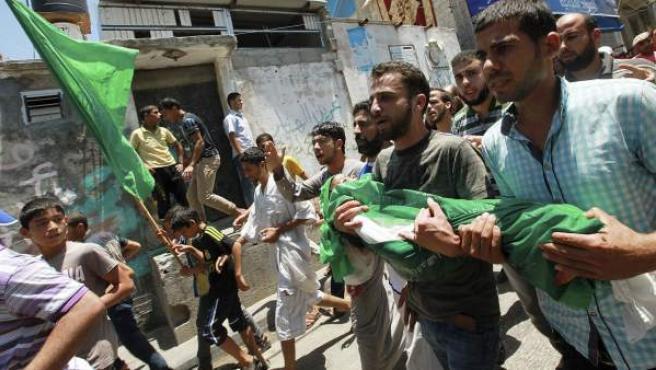 Un grupo de palestinos traslada el cuerpo del niño de tres años Mohammed Mnassrah, fallecido junto a su familia en los bombardeos israelíes, durante su funeral en el campo de refugiados de Al Maghazi en la Franja de Gaza