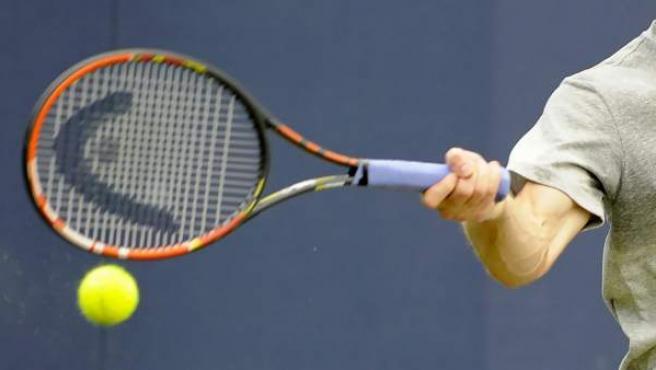 Un jugador golpea una pelota de tenis con su raqueta durante un entrenamiento.