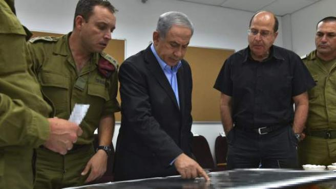 Fotografía facilitada por las Fuerzas Armadas israelíes que muestra al primer ministro israelí, Benjamín Netanyahu (c), y al ministro de Defensa israelí, Moshe Yaalon (2d), durante su visita al Comando Sur del ejército israelí, en una localización no facilitada de Israel.