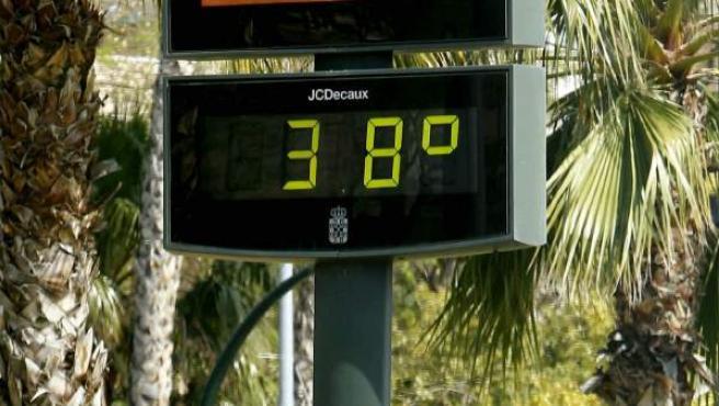 Un motorista circula ante un termómetro que marca 38 grados centígrados, en la avenida Juan Carlos I de Murcia.