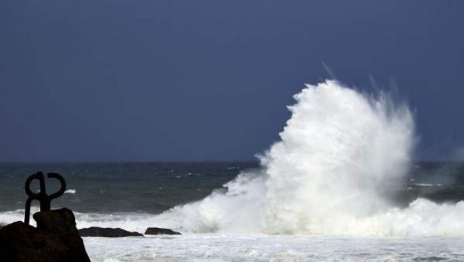 Una ola rompe junto a la obra de Chillida 'El peine del Viento', en San Sebastián.