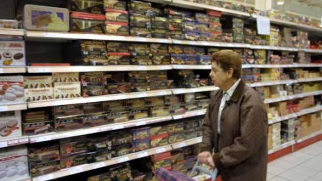 Una mujer observa una estantería repleta de productos en un supermercado.