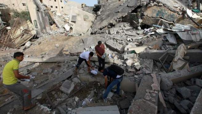 Un grupo de palestinos revisa los restos de los escombros provocados por un bombardeo israelí en Gaza.