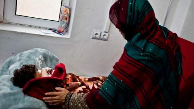 Un mujer acompaña a su hija en un hospital afgano.