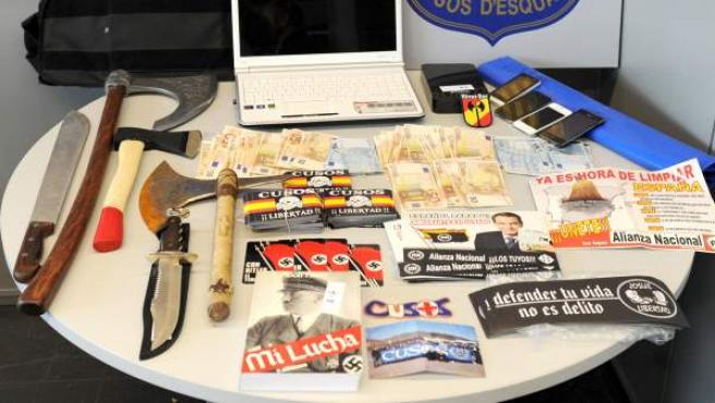 El material fascistas, las armas blancas y el dinero en efectivo encontrados en domicilios de miembros de los Cusos acusados de extorsionar a un vecino de Tarragona.