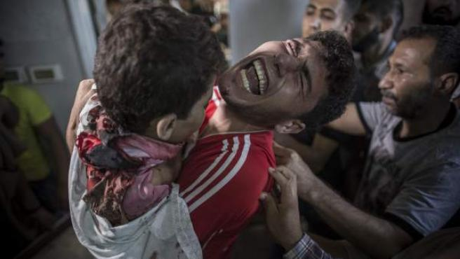 Un hombre palestino llora mientras sujeta el cuerpo sin vida de su hermano pequeño que ha muerto en un bombardeó naval isralí en el puerto de Gaza, en el depósito de cadáveres del hospital Shifa, en Gaza.