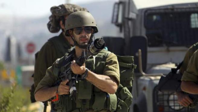 Varios soldados israelíes lanzan gas lacrimógeno contra los palestinos, durante una manifestación en contra de los ataques israelíes en la franja de Gaza, en el punto de vigilancia Huwwara, cerca de la ciudad cisjordana de Nablus