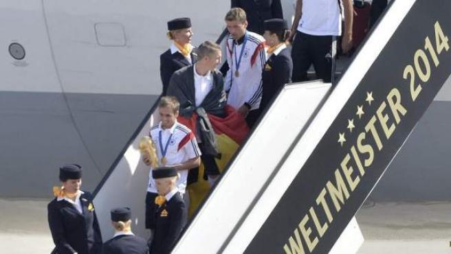 El capitán de la selección alemana de fútbol, Philipp Lahm (c), desciende del avión con la Copa del Mundo de la FIFA, a la llegada del combinado al aeropuerto berlinés de Tegel a su regreso de Brasil, en Berlín (Alemania).