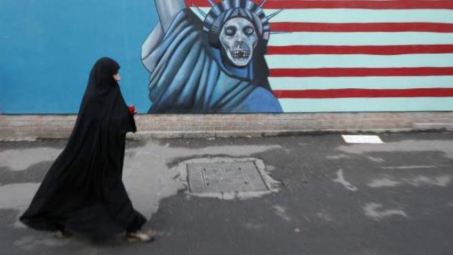 Una mujer iraní-de pies a cabeza con velo pasa junto a un dibujo satirizado de la Estatua de la Libertad, pintado en la pared de la antigua embajada de EE.UU. en Teherán.
