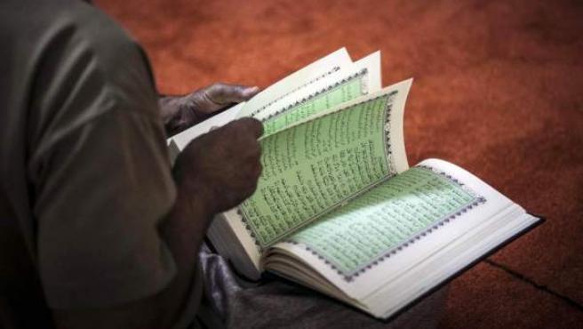 Una persona sostiene en su regazo el Corán, el libro sagrado del Islam.