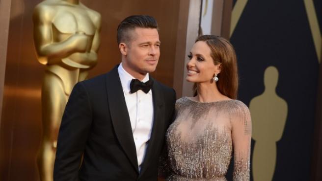 Brad Pitt y Angelina Jolie posan sonrientes ante los medios durante la alfombra roja de los Oscar 2014.