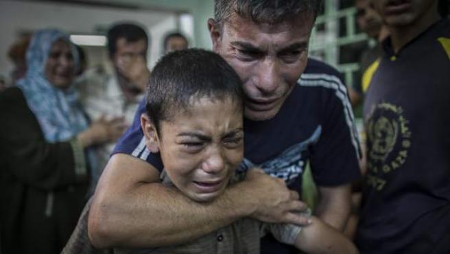 Varias personas lloran la muerte de un familiar, que fue asesinado en el bombardeo israelí a la escuela de la localidad de Beit Hanún, en el hospital de Kamal Adwan en Beit Lahiya en Gaza