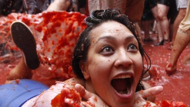 Una joven disfruta del caldo que se ha formado entre el jugo de los tomates de la guerra de la Tomatina y la lluvia.