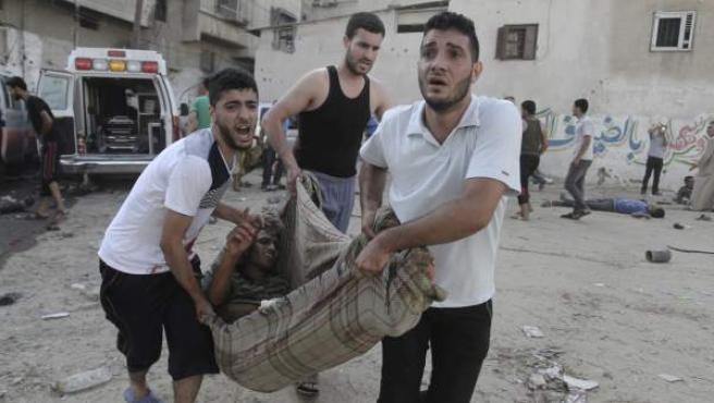 Unos hombres llevan en una manta a un palestino herido en el bombardeo a un mercado.