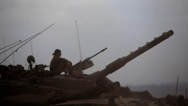 Un soldado israelí descansa sobre un tanque Merkava cerca a la frontera con al Franja de Gaza, al sur de Israel.