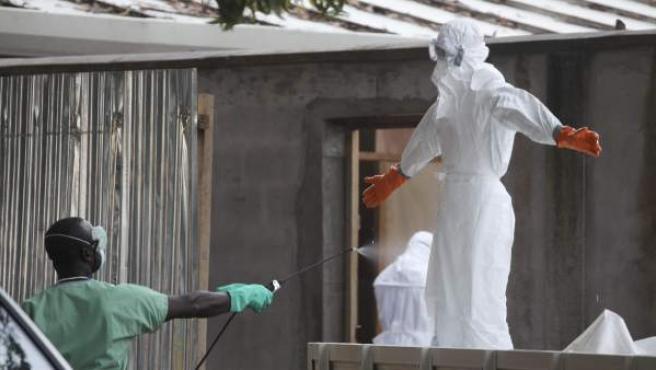 Imagen que muestra a enfermeras de Liberia protegidos con ropas especiales y desinfectándose después de tratar a varias víctimas afectadas con ébola en un hospital de Monrovia, Liberia.