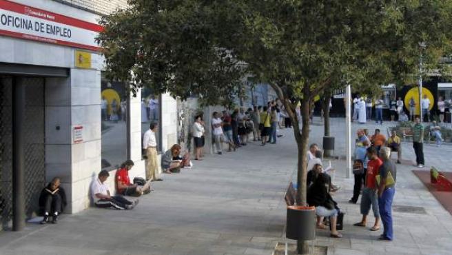 Personas esperando a que abra una Oficina de Empleo.