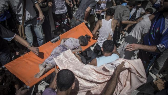 Unos palestinos recuperan el cuerpo de una niña de ocho años fallecida durante un ataque israelí en el campo de refugiados de Shati, en la ciudad de Gaza (Franja de Gaza). El ataque se produjo poco después de entrar en vigor una tregua humanitaria que Israel había anunciado, según informó un portavoz palestino. El ataque alcanzó la vivienda de la familia al-Bakri, donde murió una de las hijas y otras 30 personas resultaron heridas por lo que que fueron trasladadas al hospital Shifa.