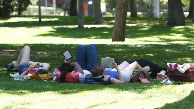 Varias jóvenes se refugian en la sombra del intenso calor en Madrid.