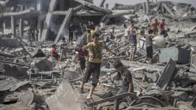 Un joven palestino corre sobre los escombros de lo que antes era una mezquita, destruida por un ataque israelí en Gaza.