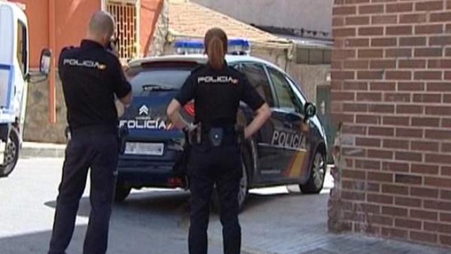 Dos policías en las inmediaciones de la vivienda donde una mujer de 39 años ha sido hallada muerta en Orihuela.