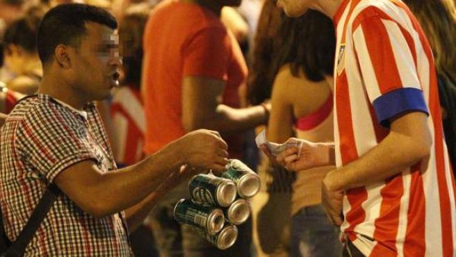 Un 'latero' vendiendo cervezas a un joven en una aglomeración de personas en Madrid.