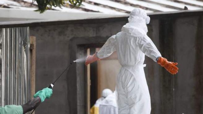Una enfermera siendo desinfectada en Liberia, tras preparar varios cadáveres del virus del Ébola para ser enterrados.