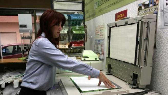 Una mujer haciendo unas fotocopias.