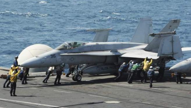 Varios miembros de la Marina guiando a un avión Hornet F/A 18 para su despegue desde la cubierta del portaaviones George H.W. Bush, en el Golfo Pérsico, este viernes 8 de agosto del 2014.