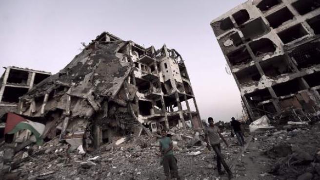 Palestinos caminan entre los escombros de lo que fueron las torres de AL-Nada, en el pueblo de Beit Lahiya, al norte de la Franja de Gaza.