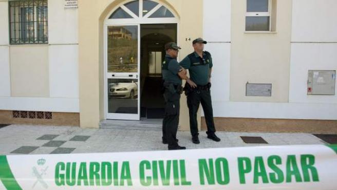 Agentes de la Guardia Civil en la puerta del bloque en la barriada Conejito de Torrox donde ha sido hallada muerta Ana María Márquez.