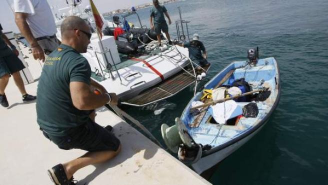 Un agente del Servicio Marítimo de la Guardia Civil amarra una de las pateras en un pantanal del puerto de Torrevieja.