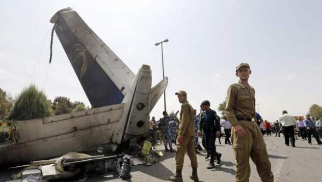 Agentes de la policía iraní inspeccionan la cola del avión de pasajeros que se estrelló al poco de despegar de un aeropuerto de Teherán.