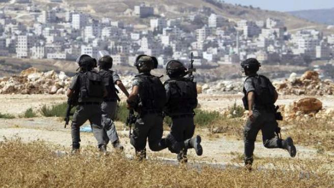 Varios soldados de las fuerzas israelíes toman posiciones durante un enfrentamiento con palestinos cerca de un control de seguridad en Bet Forik, en la ciudad cisjordana de Nablus.