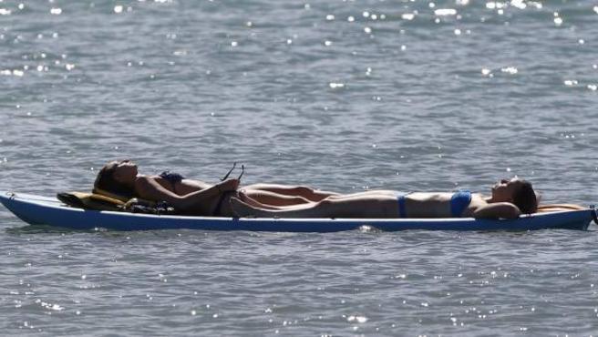 Dos jóvenes toman el sol en el mar.