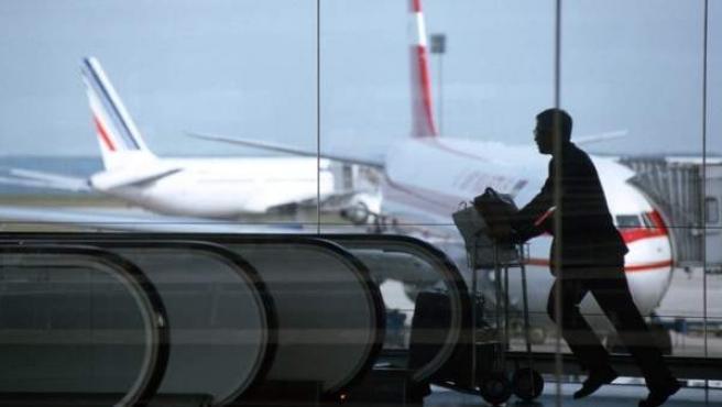 Un hombre corriendo con su equipaje por un aeropuerto.