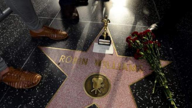 Un grupo de personas rodea un ramo de flores y una estatuilla del premio Óscar sobre la estrella del actor estadounidense Robin Williams en el Paseo de la Fama.