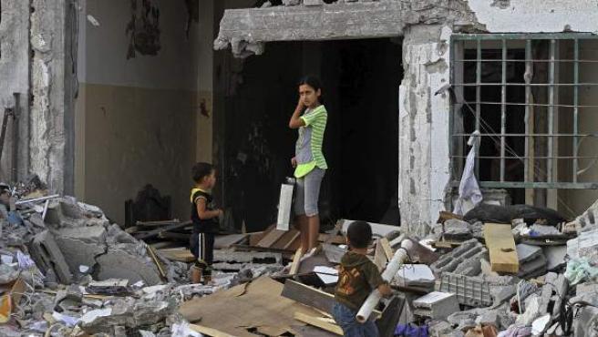 Niños palestinos inspeccionan los escombros de un edificio destruído durante una ofensiva israelí en Beit Lahiya, al norte de la Franja de Gaza, este viernes 15 de agosto de 2014.