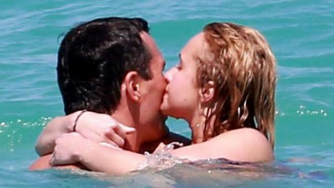 Una pareja se abraza en el agua del mar.