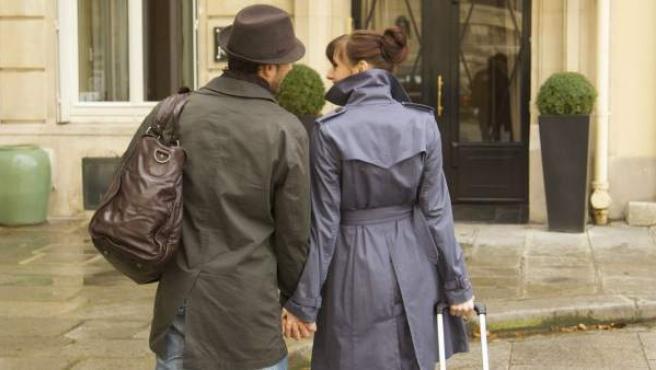 Una pareja de turistas, llegando a la entrada de un hotel.